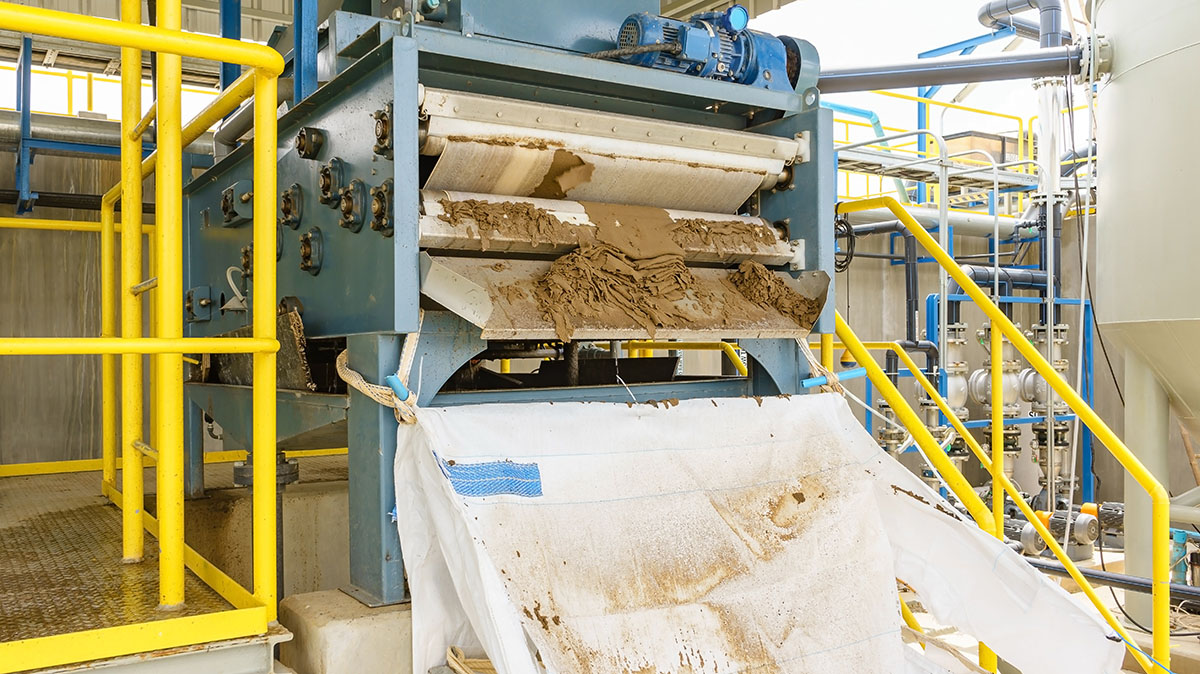 Sludge press producing pressed solids from waste water for disposal.
