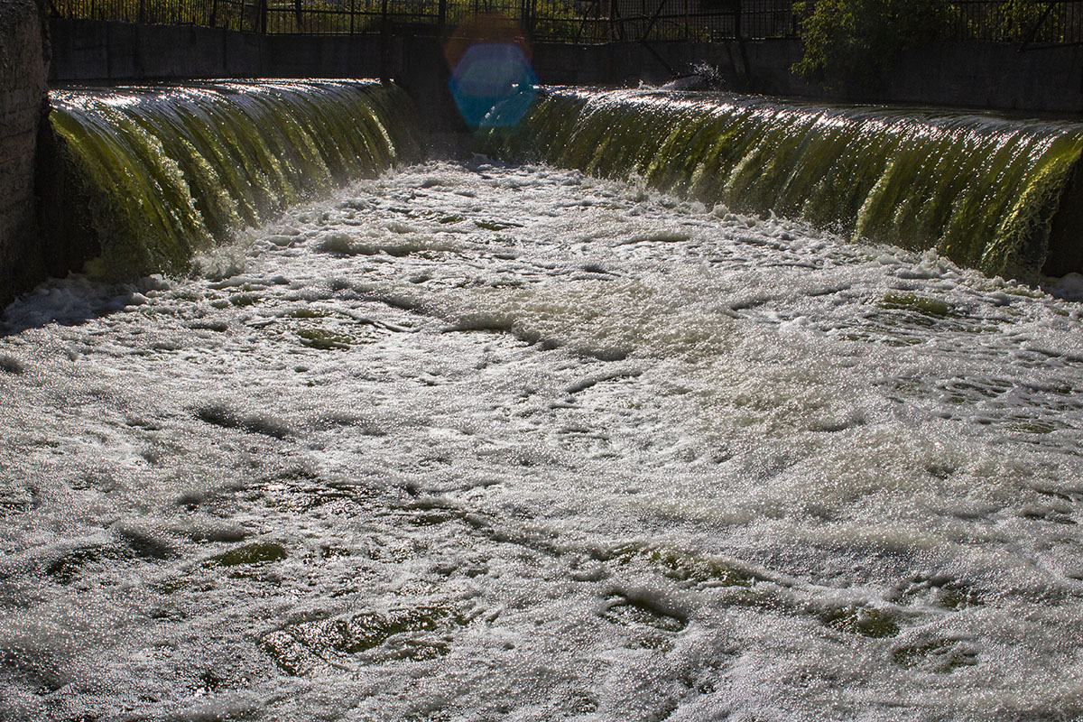 Municipal wastewater flowing over weirs on two sides of a rectangular pretreatment basin where products are added to assist in removing contaminants by downstream processing before discharge to a river.