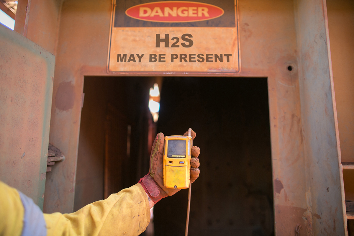 """A person's arm shown extended in front of them holding a yellow hand size gas detection meter in front of a walking entrance into a concrete structure that could contain high levels of hydrogen sulfide gas. A large """"Danger H2S may be present"""" sign is above the entrance."""
