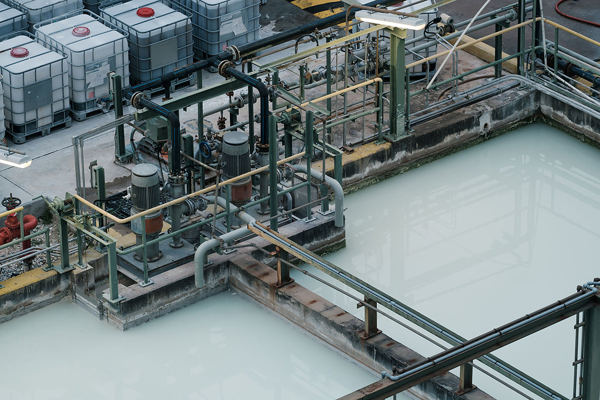 Rectangular pit with gray water, vertical mixer motors, and arranged piping
