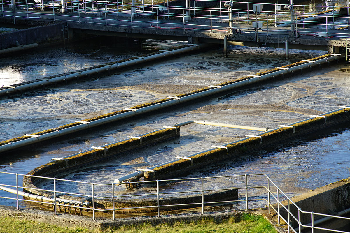 Large process water clarification and contaminant removal basin system. It has a back and forth flow design and shows the surrounding protective railings as well as the influent piping and man-walk with railings above the basin.