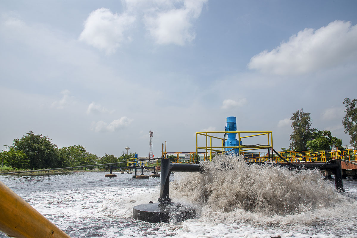 One acre size aeration basin with pumps that aggressively agitate the surface of the wastewater in the basin upward into the air near the pumps, driving oxygen into the water to help consume the contamination in the water.