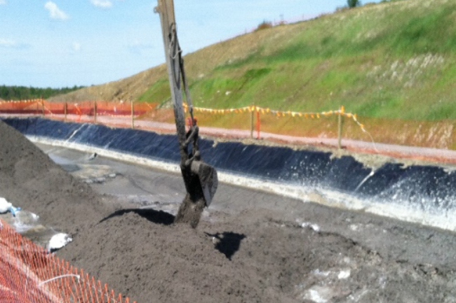 rectangular lined earthen pit with long-stick excavator bucket moving gray solids